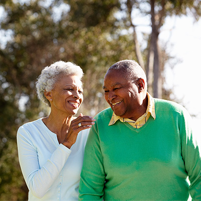 Senior African American man with chronic disease walking outside with wife