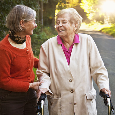 Senior caucasian woman with chronic disease and friend going for a walk outdoors