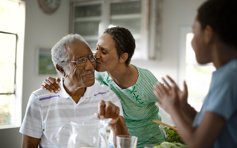 Elderly African American man enjoying time with family in kitchen